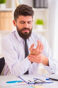 Male professional that is experiencing hand pain and hand neuropathy