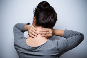 Woman that is experiencing neuropathy problems in her upper back and neck