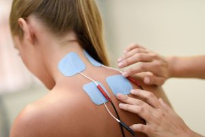 Woman receiving electrostimulation therapy for neuropathy in her neck and back
