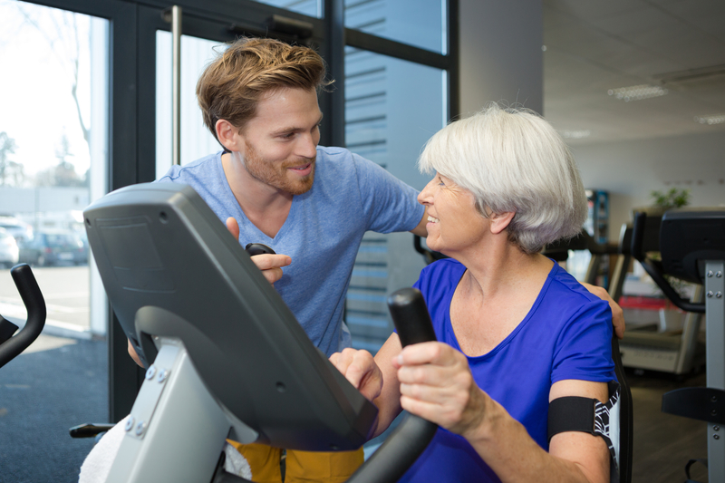 Older woman patient talking with a chiropractic and physical therapist as she is on an exercise machine