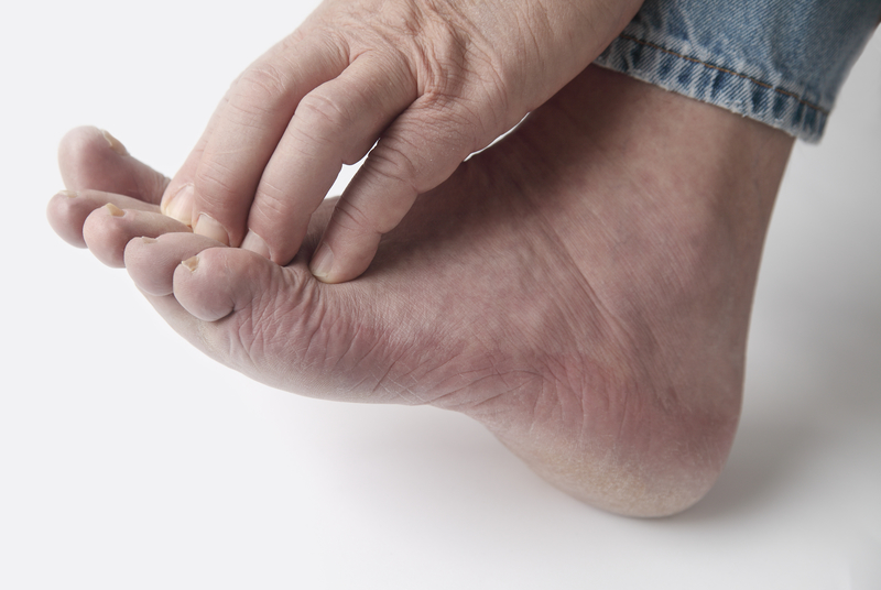 A person experiencing neuropathy symptoms in their foot